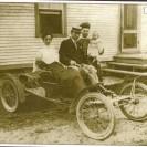 Nous apercevons Délia Péloquin, soeur de Zoël, et Charles Désellier venus des U.S.A. dans cette voiture entre 1906 et 1909. L'épouse de Zoël Péloquin, Marie Gagné, tient dans ses bras Yvonne, soeur de Conrad Péloquin. Cette photographie a été prise chez Zoël et Narcisse Péloquin propriétaires de la ferme de François Delude, l'actuel propriétaire au 1841 sur la route 112.
