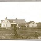 """Voici la propriété de Jacob Dumas, photographié en 1915 près de sa maison avec son fils Ovila à qui il est sur le point de transmettre cette ferme. Nous voyons Ovila, à l'avant de la photo,  creusant la cave d'une autre maison que Jacob fera déménager et qui deviendra sa demeure pendant ses vieux jours et, plus tard, celle de Renaud Barolet. Située au bout de la rue St-Janvier dans le vieux village, cette ferme acquise par Ovila a vu naître ou grandir les enfants d'Ovila. Gérard Côté et René-Paul Bernier en ont été propriétaires par la suite. Cette maison """"pièces sur pièces"""" a été déménagée au 101 chemin Magnan dans les années 70."""