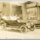 """Quel plaisir de faire une randonnée en famille en automobile """"convertible"""". Nous sommes sur la rue Centrale, appelée aujourd'hui 9e avenue. À l'avant du véhicule, nous pouvons voir Adélard Laplante, Amélia Paradis son épouse et leur enfant Renée-Paule Laplante."""
