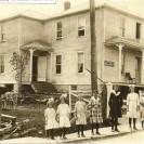 Cette grande maison a été bâtie au début du siècle par un monsieur Beaupré sur la rue St-Janvier dans le vieux village vis-à-vis le moulin Beaudoin. Voici sa photographie prise en 1911, année où la famille Joseph Beaudry et Lumina Maria Dion y habitait et où cette propriété servait de commerce d'engins, de machineries et de voitures. Elle fut habitée aussi par une famille Proulx. Déménagée par Mathias Caron dans Weedon Station sur le site d'une scierie en 1932, elle a été la propriété de Georges Fontaine, de Mathias Caron et de Jos. Denis avant d'être la propriété de Henri et de Alvine Rousseau en 1944. C'est là que les transactions de billots et les ventes de bois de construction se faisaient. Aujourd'hui, Alvine et sa fille Yvette y demeurent encore.