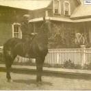 René Tanguay est fier de monter un joli cheval de selle. Il est photographié devant la maison de son père Adolphe Tanguay vers les années 1925.