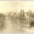 """Au loin, nous apercevons M. Tanguay. Sur la deuxième voiture, ce sont Adélard Bouffard et son épouse. À l'avant, nous remarquons un attelage de trois chevaux tirant une voiture charroyant du minerai qui vient de la mine """"Weedon Piryte and Copper"""". Zéphirin Després en est le conducteur."""