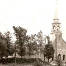 Nous voyons l'ensemble église et presbytère de la paroisse St-Janvier aux décennies où les arbres étaient nombreux sur le terrain de l'école.