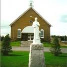 Voici une autre photographie de l'église de la paroisse où on retrouve la statue de son patron en avant-plan.