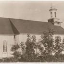 L'église St-Janvier est sur le point d'arriver sur son site. Elle a dû faire un arrêt d'environ une semaine sur le terrain d'un certain William Galipeau, c'est-à-dire près de la pharmacie actuelle, puisque les fondations qui devaient la recevoir n'étaient pas prêtes.